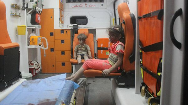 5-year-old Omran Daqneesh and his sister sit in an ambulance after being pulled out of a building hit by an airstrike in Aleppo, Syria, on Aug. 17, 2016 - Sputnik Mundo