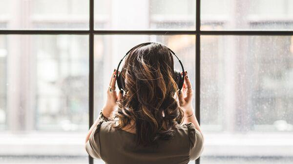 Una mujer con auriculares (imagen ilustrativa) - Sputnik Mundo