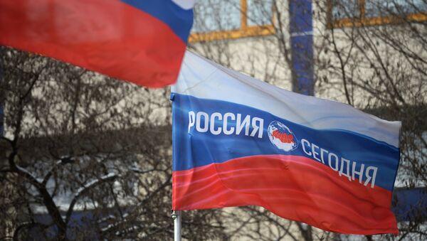 Bandera rusa con el logotipo de la Agencia de Información Internacional Rossiya Segodnya - Sputnik Mundo