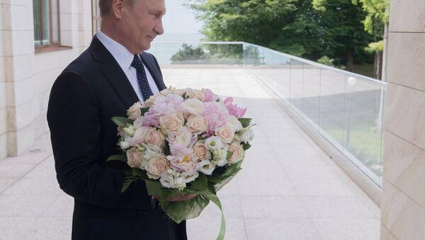 Vladímir Putin, presidente de Rusia, con un ramo de flores - Sputnik Mundo