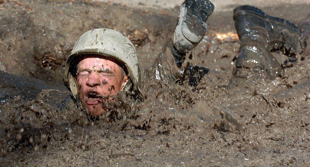 Un soldado de EEUU caído en un charco con barro
