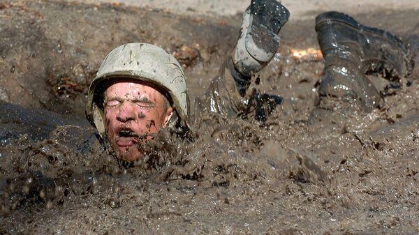 Un soldado de EEUU caído en un charco con barro - Sputnik Mundo