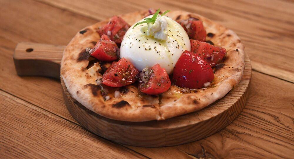 Focaccia hecha al horno con tomates y albahaca en el restaurante Quesería