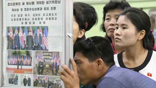 Los norcoreanos leen en un periódico sobre la cumbre entre EEUU y Corea del Norte - Sputnik Mundo