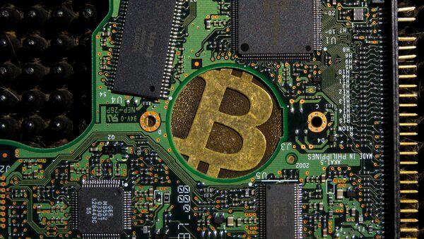 Un signo de bitcóin en una placa de computadora - Sputnik Mundo