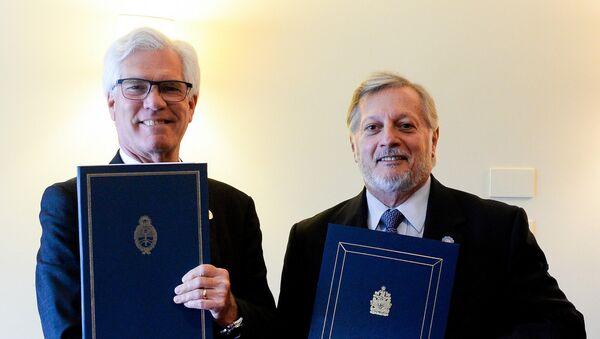Ministros de energía de Argentina y Canadá durante la firma de acuerdos bilaterales en Bariloche - Sputnik Mundo