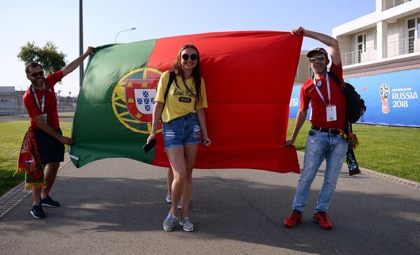 Fans of Portugal's team posing in front of the country's flag ahead of a group stage World Cup match between Spain and Portugal. - Sputnik Mundo