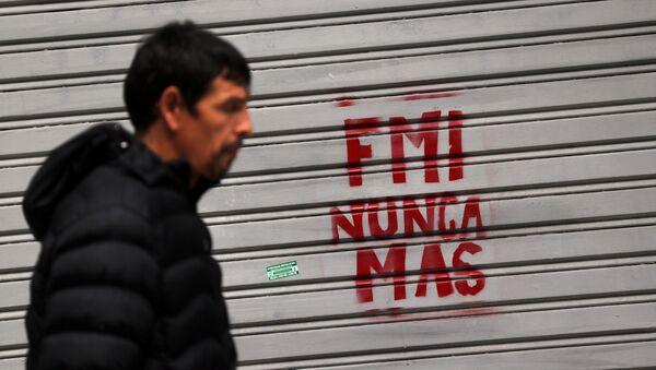 Un hombre camina frente a un grafiti de protesta contra el FMI - Sputnik Mundo