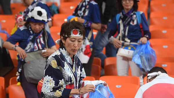 Los hicnhas de Japón limpian el estadio tras el partido con Senegal - Sputnik Mundo
