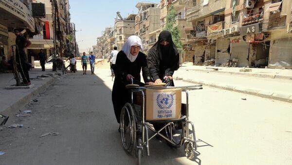 Refugiados palestinos con la ayuda humanitaria de la UNRWA (archivo) - Sputnik Mundo