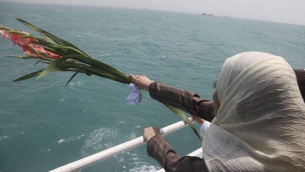 Una mujer iraní echa flores en el Golfo Pérsico durante una ceremonia que recuerda a los 290 pasajeros del vuelo 655 de Iran Air - Sputnik Mundo