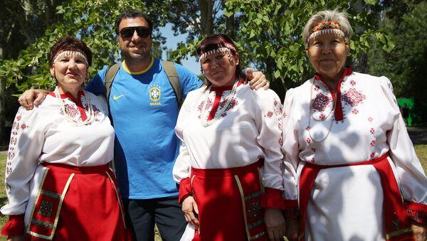 Un hincha brasileño se toma una foto con mujeres vestidas con atuendos típicos en la fiesta de Sabantuy, en Samara. - Sputnik Mundo
