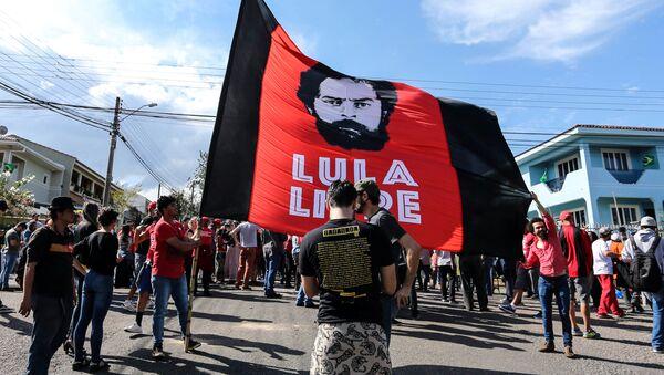Partidarios del expresidente brasileño Luiz Inácio Lula da Silva sostienen una bandera junto al edificio de la Policía, en Curitiba. - Sputnik Mundo