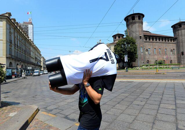Un hombra carga un maniquí con la camiseta de Cristiano Ronaldo en Turín