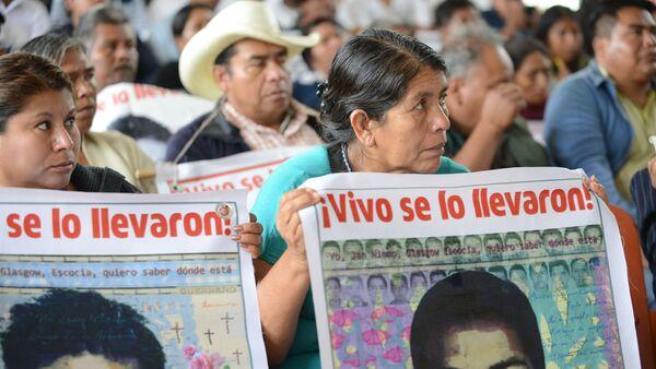 Personas sostienen carteles que recuerdan a los 43 desaparecidos de Ayotzinapa, en una visita de la Comisión Interamericana de Derechos Humanos a la escuela normal en la que estudiaban, en 2015. - Sputnik Mundo