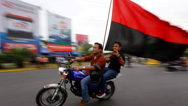 Dos motociclistas con una bandera del Frente Sandinista de Liberación Nacional de Nicaragua. - Sputnik Mundo