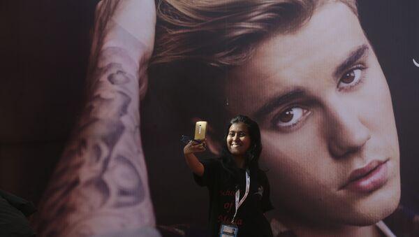 Una fan del cantante canadiense Justin Bieber se hace un selfi delante de una fotografía del astro - Sputnik Mundo