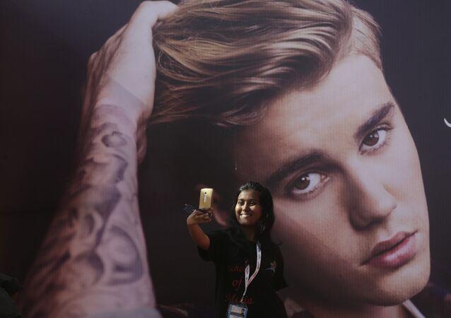 Una fan del cantante canadiense Justin Bieber se hace un selfi delante de una fotografía del astro