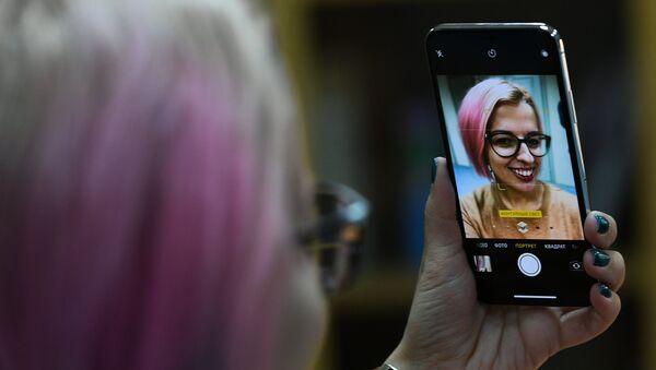 Una chica se hace una selfi con un iPhone X - Sputnik Mundo