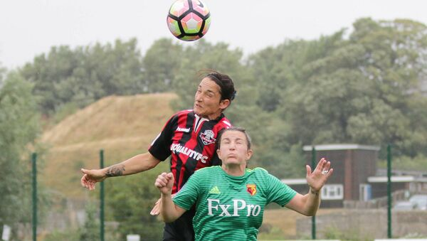 Dos futbolistas saltan para alcanzar la pelota - Sputnik Mundo