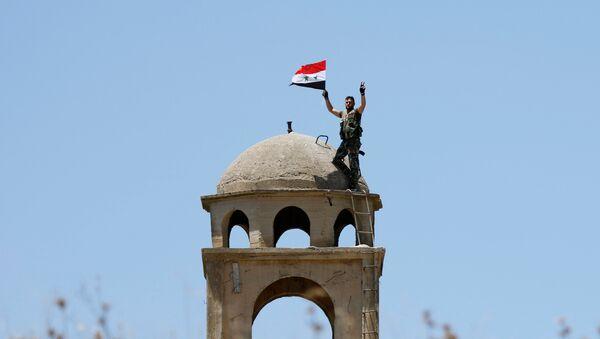 Un soldado sirio con su bandera - Sputnik Mundo