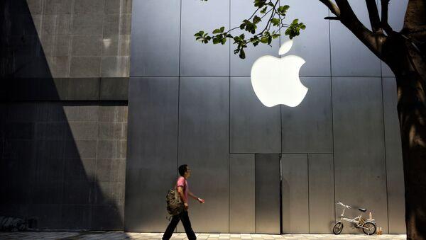 Un hombre camina al lado de una recién abierta tienda de Apple - Sputnik Mundo