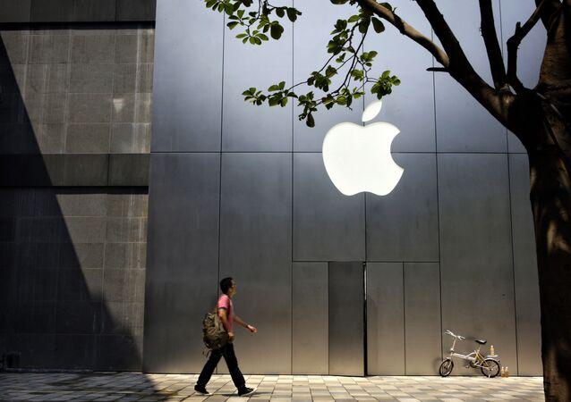 Un hombre camina al lado de una recién abierta tienda de Apple