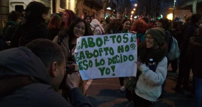 Mujeres sosteniendo un cartel durante la manifestación en Montevideo en apoyo  al aborto seguro, legal y gratuito en Argentina.