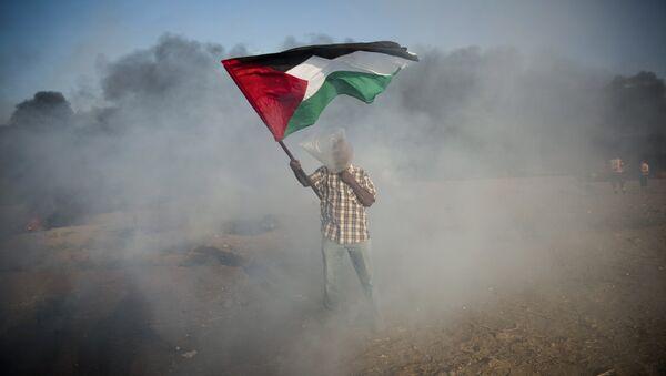 Un palestino con la bandera durante las protestas en Gaza - Sputnik Mundo