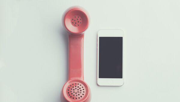 Un teléfono inteligente y un auricular - Sputnik Mundo