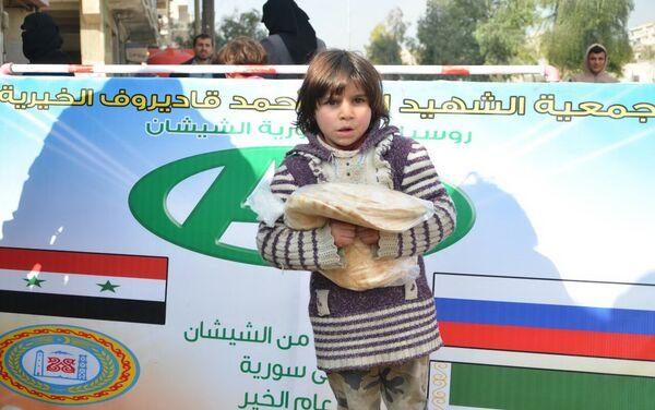 Un niño sirio con el pan que acaba de recibir en el punto de entrega de la ayuda humanitaria - Sputnik Mundo