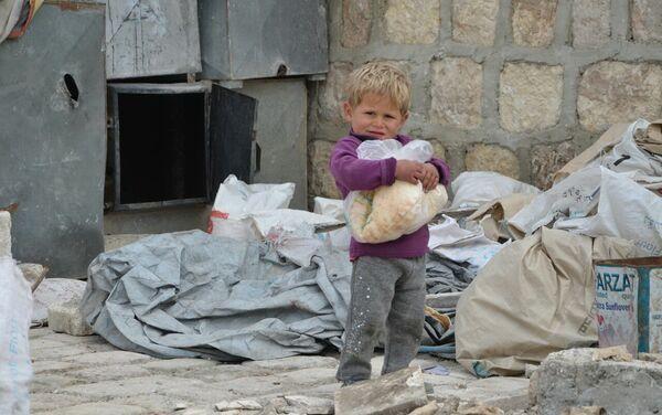 Un niño sirio en Alepo con el pan distribuido por la Fundación Pública Local Ajmat Kadírov - Sputnik Mundo