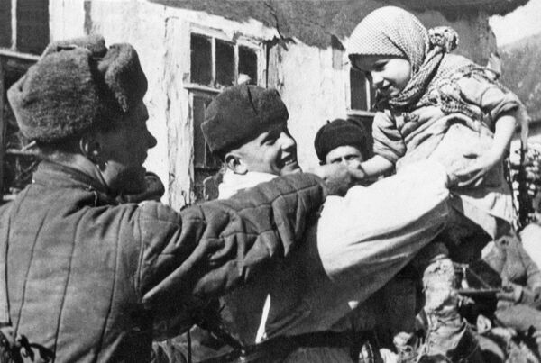 Soldados del Ejército Rojo con los habitantes de un pueblo liberado tras la batalla de Kursk (1943) - Sputnik Mundo