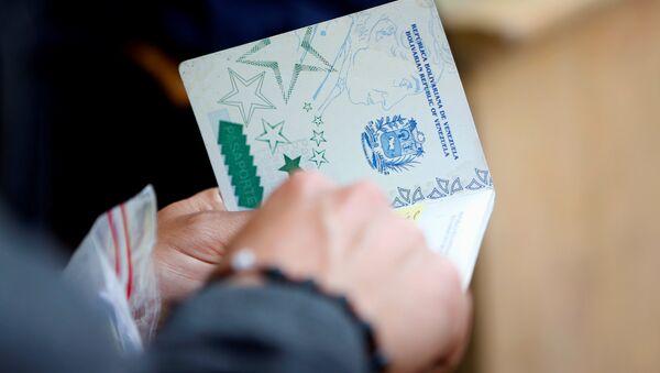 Un migrante venezolano muestra su pasaporte - Sputnik Mundo