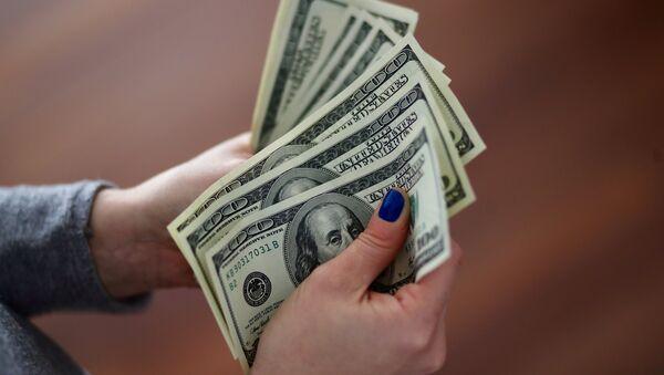 Una mujer cuenta los billetes de un dólar - Sputnik Mundo
