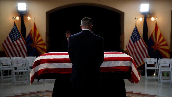 Una persona delante del ataúd del senador John McCain - Sputnik Mundo