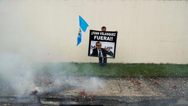 Un manifestante sostiene un cartel frente a la sede de la CICIG en Guatemala - Sputnik Mundo
