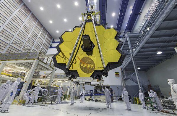 En esta foto los técnicos levantan el espejo del telescopio espacial James Webb utilizando una grúa en el Centro de Vuelo Espacial Goddard en Greenbelt, Maryland, en 2017. - Sputnik Mundo