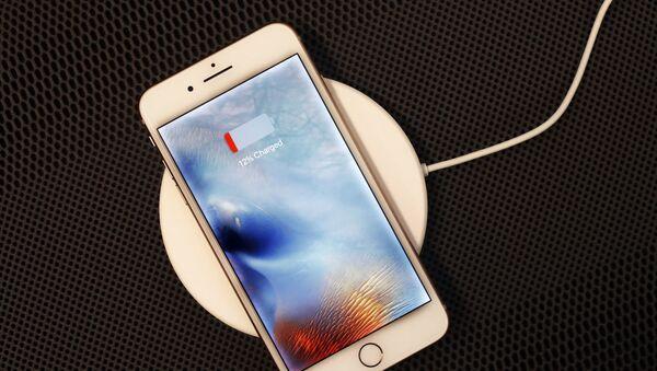 Un iPhone 8 Plus descansa en un cargador inalámbrico en Nueva York.  - Sputnik Mundo
