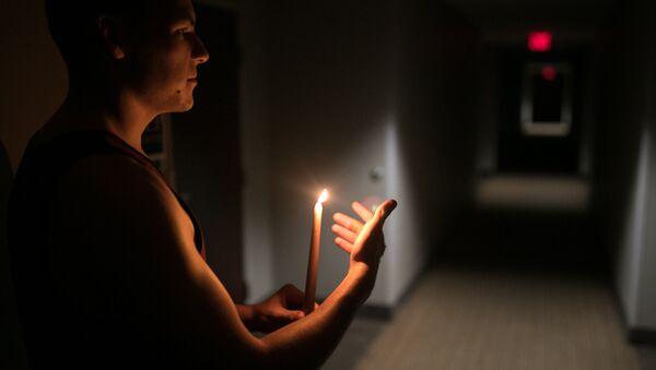 Hombre con una vela durante el huracán Florence - Sputnik Mundo