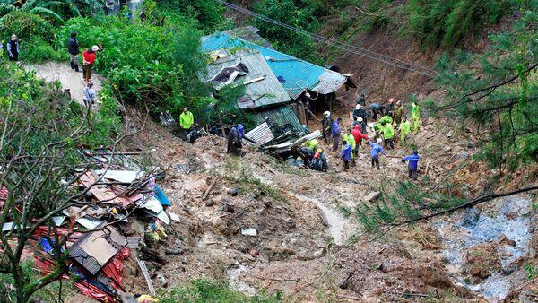Unos rescatistas buscan a tres ciudadanos enterrados por un deslizamiento durante el tifón Mangkhut - Sputnik Mundo