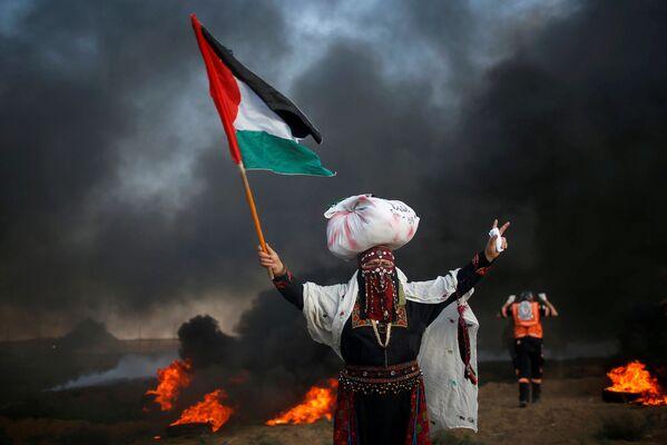 Una mujer con la bandera de Palestina, durante una manifestación al lado de la frontera con Israel. - Sputnik Mundo