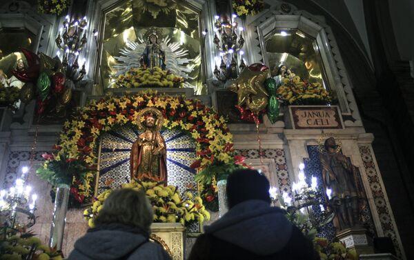 Dos creyentes rezan frente a la imagen de San Judas Tadeo en el Templo de San Hipólito, en la Ciudad de México - Sputnik Mundo