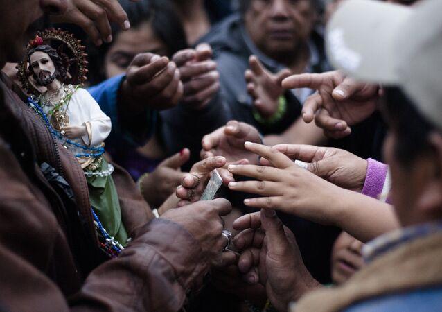Fieles reciben imágenes de San Judas Tadeo que se reparten fuera del Templo de San Hipólito en la Ciudad de México