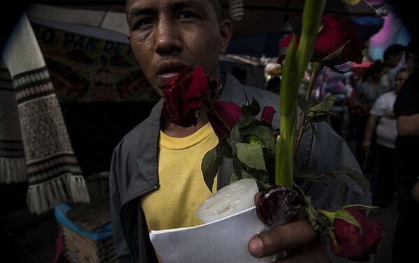 Hombre muestra los regalos recibidos por los demás fieles que reparten flores, dulces e imágenes - Sputnik Mundo
