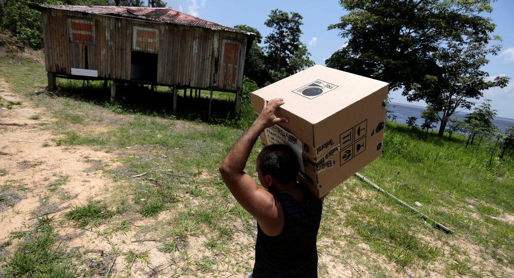 Un obrero lleva la caja urna de votación a una comunidad en el río Amazonas