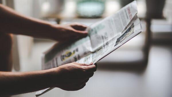 Una persona con un periódico en las manos - Sputnik Mundo