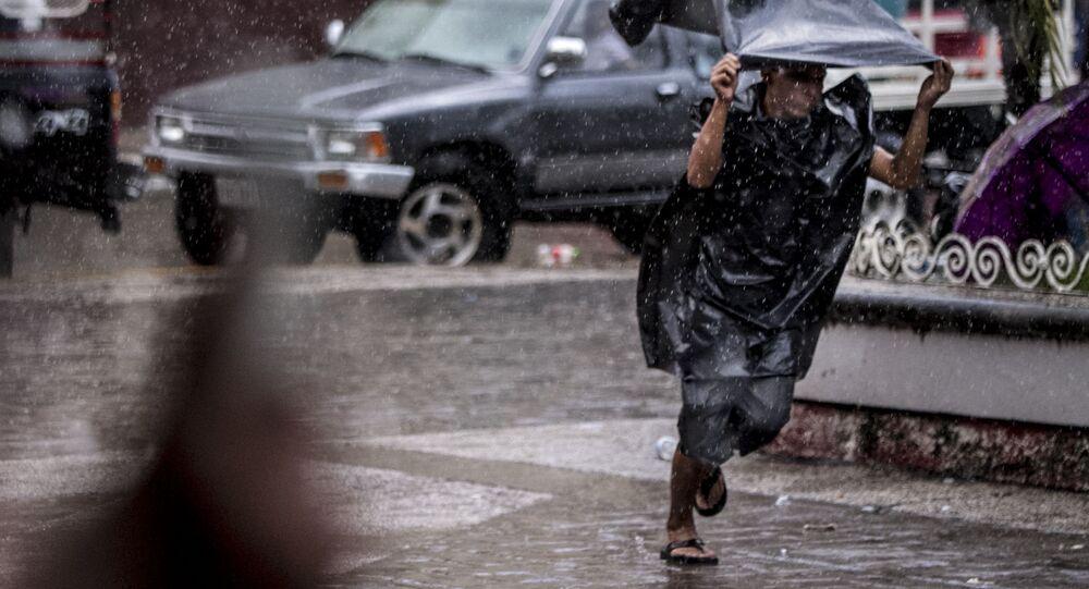 Migrante centroamericano corre de la lluvia y en el parque Miguel Hidalgo de Tapachula