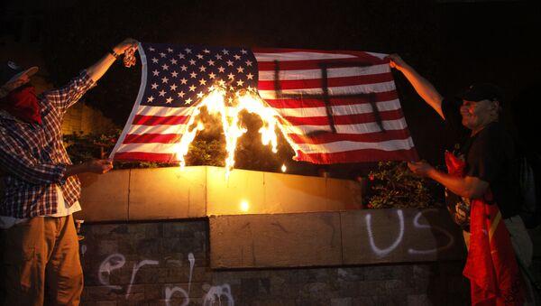 Dos personas están quemando una bandera de Estados Unidos durante una protesta a favor de la caravana de migrantes frente a la embajada estadounidense en Tegucigalpa, Honduras - Sputnik Mundo