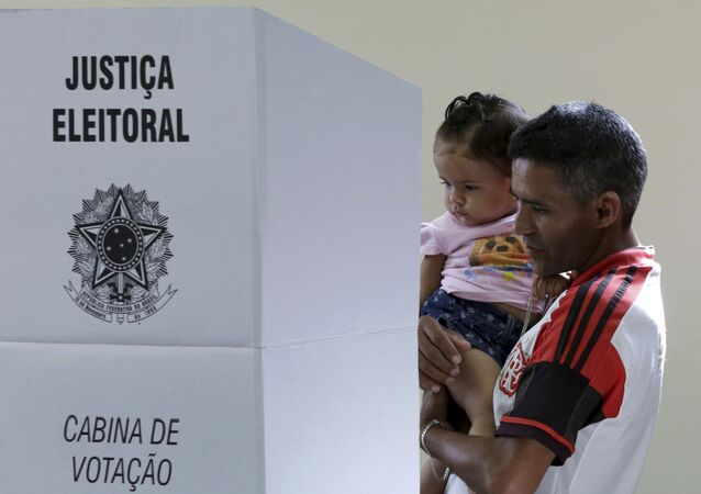 Un hombre vota con su hija en Brasil